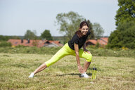 Woman doing stretching excersice on meadow - DIGF04357