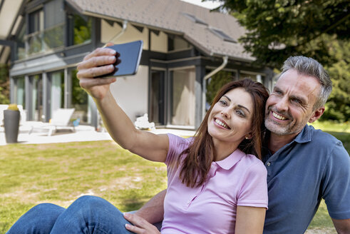 Happy couple sitting in garden of their home taking a selfie - DIGF04369