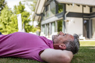 Mature man lying in garden of his home - DIGF04372
