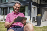 Smiling mature man sitting in garden of his home using a tablet - DIGF04375