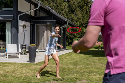 Happy couple playing with flying disc in garden of their home - DIGF04378