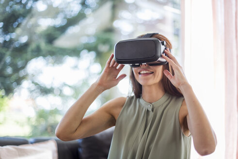 Smiling woman at home wearing VR glasses - DIGF04381