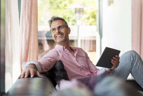 Smiling mature man sitting on couch at home holding a tablet - DIGF04384