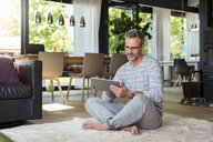 Mature man sitting on carpet at home using a tablet - DIGF04393