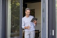 Smiling mature standing at French door at home using a tablet - DIGF04396