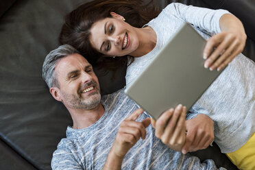 Happy couple lying on couch at home sharing a tablet - DIGF04405