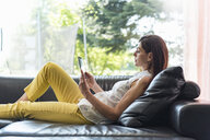 Woman lying on couch at home using a tablet - DIGF04408