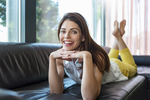 Portrait of happy woman lying on couch at home - DIGF04411