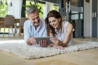 Happy couple lying on carpet at home sharing a tablet - DIGF04414