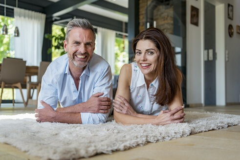 Portrait of happy couple lying on carpet at home - DIGF04417