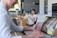 Couple at home with man using a laptop and woman reading newspaper - DIGF04435