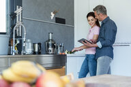Couple in kitchen at home using a tablet - DIGF04438
