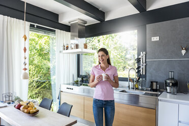 Laughing woman at home in kitchen with cup of coffee - DIGF04447