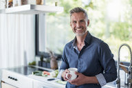 Portait of smiling mature man at home in kitchen with cup of coffee - DIGF04450