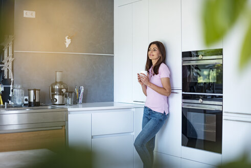Smiling woman at home in kitchen with cup of coffee - DIGF04453