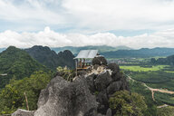 Laos, Vang Vieng, man in hut on top of rocks overlooking landscape of rice fields - AFVF00512
