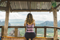 Laos, Vang Vieng, young woman in a hut overlooking landscape of rice fields - AFVF00515