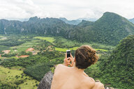 Laos, Vang Vieng, young man on top of rocks taking cell phone picture of landscape - AFVF00518