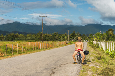 Laos, Vang Vieng, young man with bicycle in the road - AFVF00524