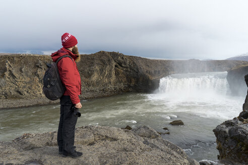 Iceland, North of Iceland, young man looking to waterfall - AFVF00530