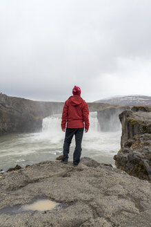 Iceland, North of Iceland, young man looking to waterfall - AFVF00533