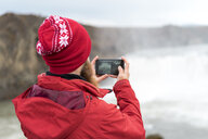 Iceland, North of Iceland, young man photographing waterfall - AFVF00536