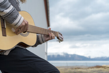 Iceland, young man playing guitar - AFVF00539