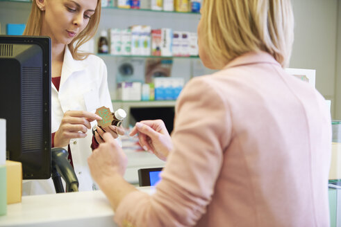 Pharmacist advising woman in pharmacy - ABIF00397