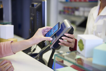 Customer paying cashless with smartphone in a pharmacy - ABIF00400