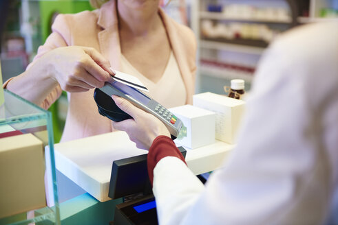 Customer paying cashless with credit card in a pharmacy - ABIF00406