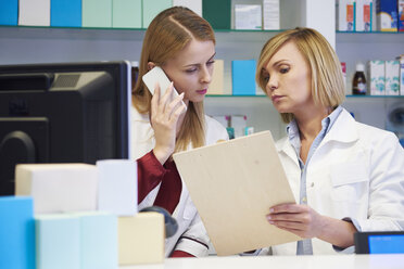 Two pharmacists at cabinet in pharmacy - ABIF00409