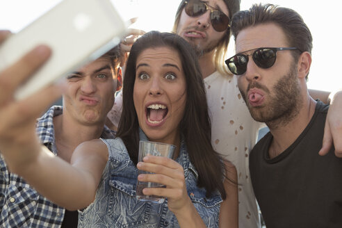 Young adult friends pulling faces for selfie at roof terrace party - ISF02209