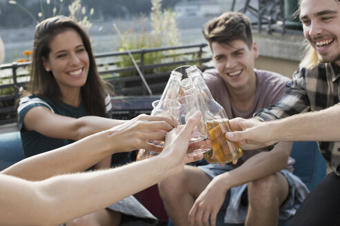 Adult friends raising a toast at roof terrace party, Budapest, Hungary - ISF02224