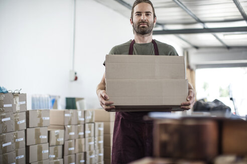 Portrait of man holding cardboard box in factory - ISF02314