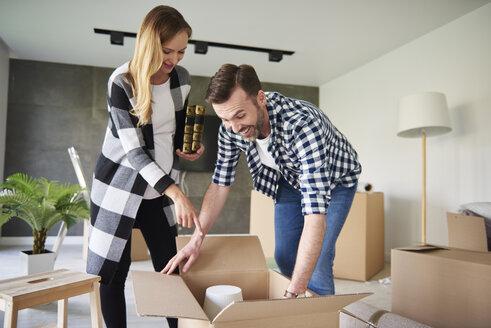 Happy couple moving into new flat unpacking cardboard box - ABIF00418