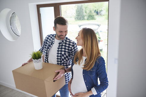 Happy man and pregnant woman moving into new flat carrying cardboard box - ABIF00424