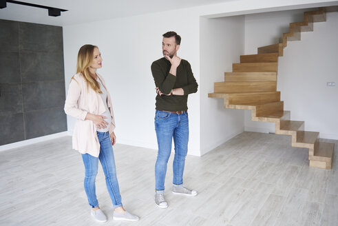 Couple standing in empty flat - ABIF00436