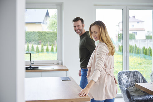 Couple examining kitchen in new flat - ABIF00439