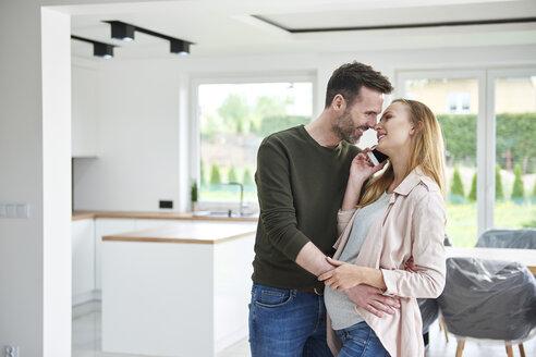 Man kissing pregnant woman in empty flat - ABIF00442