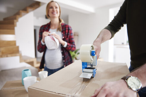 Couple moving house packing and taping cardboard boxes - ABIF00445