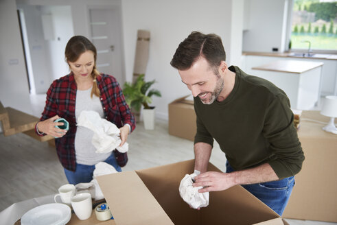 Couple moving house packing their belongings - ABIF00448