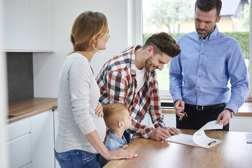 Family with real estate agent signing contract in kitchen of new apartment - ABIF00454