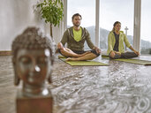 Couple practicing yoga in a room with panorama window - CVF00597