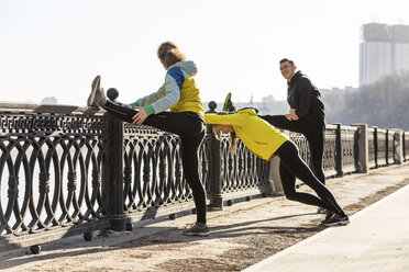 Friends doing stretching exercise on railing in the city - WPEF00299