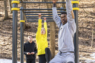 Friends exercising at monkey bars in a park - WPEF00320