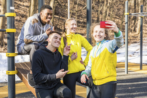Happy friends taking a selfie at fitness equipment in a park - WPEF00323