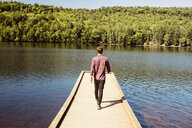 Man walking along wooden pier on lake, rear view - ISF02514