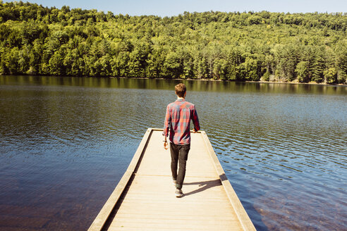 Man walking along wooden pier on lake, rear view - ISF02514
