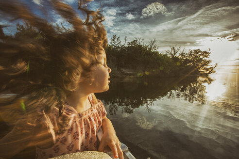 Young girl enjoying cruise on river, eyes closed basking in sunlight, Homosassa, Florida, USA - ISF02526