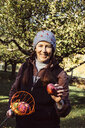 Portrait of woman holding fruit picker and fresh apple - ISF02562